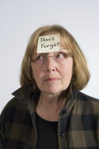 "A senior female has a quizzical look on her face, trying to remember something. To highlight that fact, there is a post it note stuck to her forehead with the words ""Don't Forget"" printed on it."